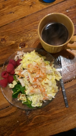 Spinach, four eggs, kimchi and raspberries with black coffee.